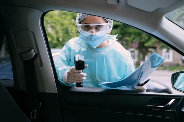 医者は体温をチェックするために赤外線温度計銃を使用します