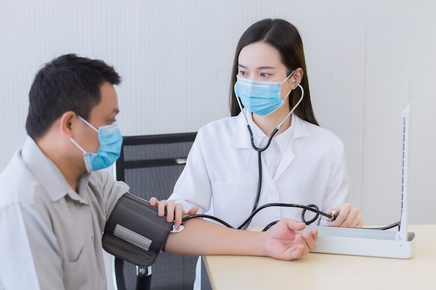 Doctor uses stethoscope and a blood pressure motoring to measure blood pressure
