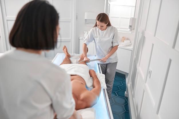 의사는 병원 사무실에서 동료와 함께 클라이언트 다리를 마사지하기 위해 도구를 사용합니다.