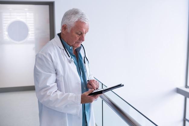 Доктор с помощью цифрового планшета в коридоре