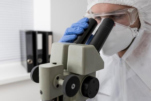 Врач с помощью микроскопа для проверки образца covid