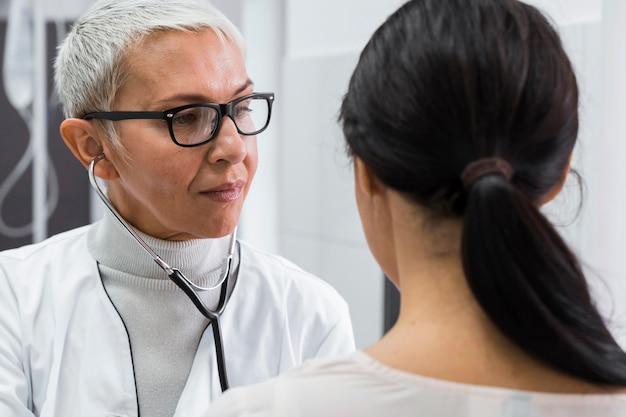 Врач с помощью стетоскопа на пациентке