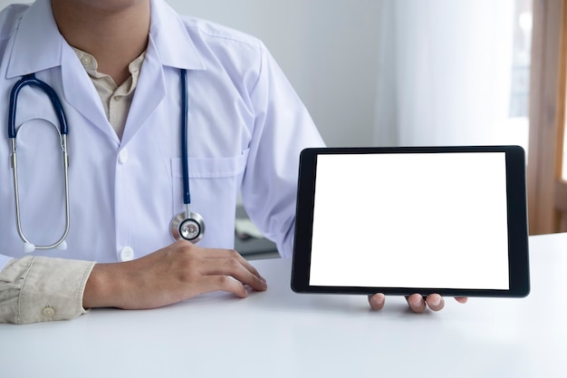 Доктор с помощью компьютерного планшета обсуждает что-то с пациентом. здравоохранение, больница и доктор концепция. скопируйте пространство пустого экрана компьютера и планшета.