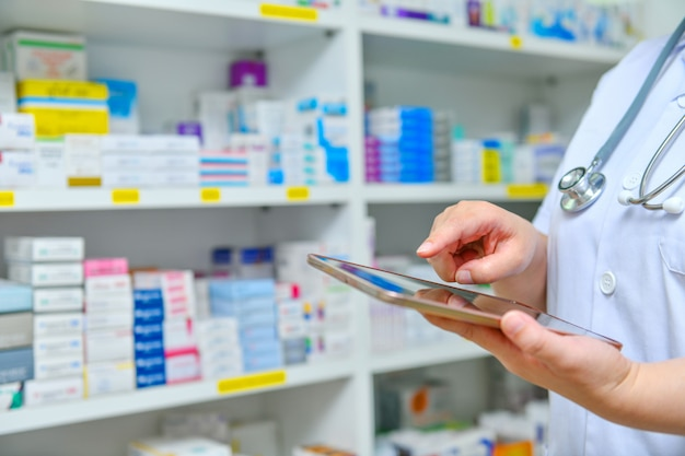 Doctor using computer tablet for search bar on display in pharmacy drugstore shelves background.online medical concept.