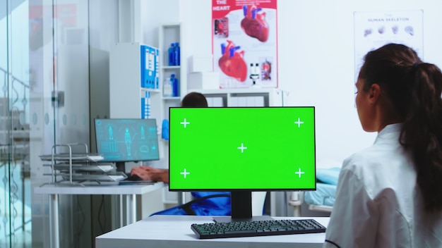 Doctor using computer with green screen mockup in hospital and assistant walks out of cabinet wearing blue uniform. medic in white coat working on monitor with chroma key in clinic cabinet to check pa