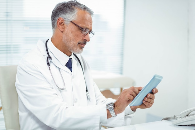 Doctor using digital tablet at clinic