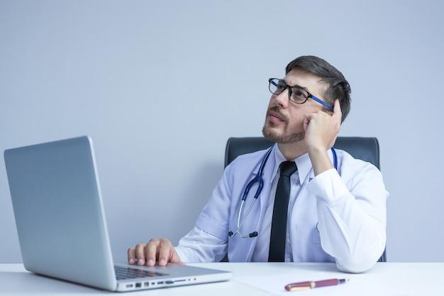 Врач с помощью цифрового планшета найти информацию об истории болезни пациента в больнице. врач с помощью стетоскопа для осмотра.