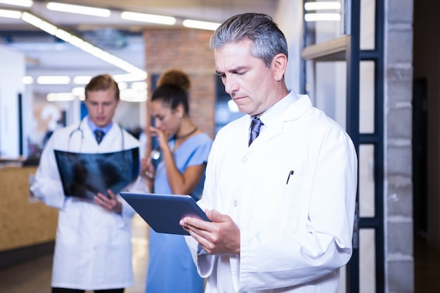 Doctor using digital tablet in hospital and colleagues standing behind and discussing