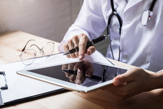 Doctor using a digital tablet in the hospital, healthcare and medicine concept.