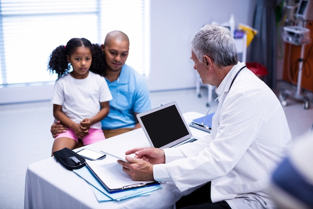 Doctor using digital tablet while interacting with patient