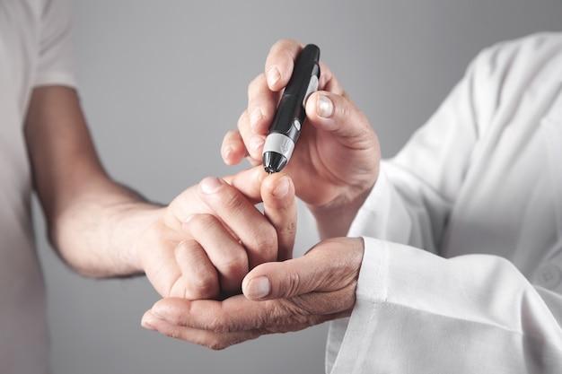 Врач с ланцетом на пальце пациента. проверка уровня сахара в крови
