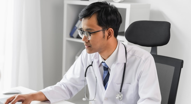 Врач с помощью ноутбука и глядя на файл отчета пациента для оценки симптомов на столе.