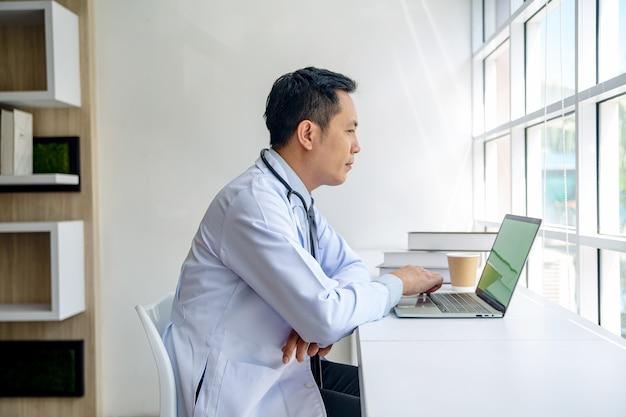 Доктор, используя ноутбук в офисе.