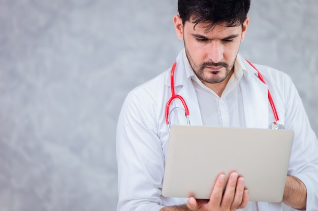 Doctor using laptop looking screen data with space