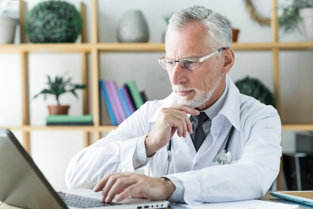 Doctor using laptop and thinking
