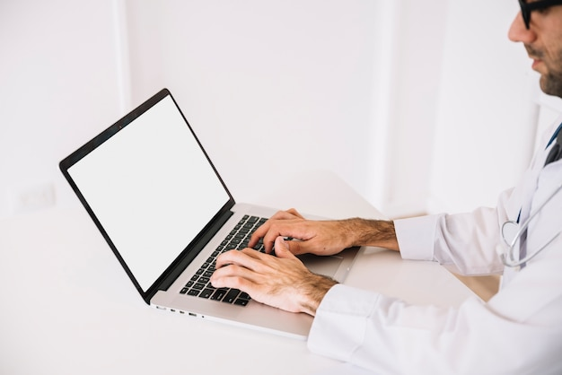 Doctor using laptop with blank white screen