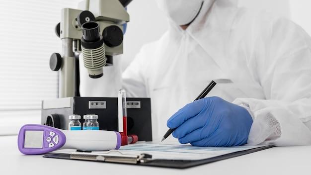 Medico che utilizza un microscopio per controllare il campione covid