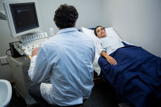초음파 검사기를 사용하는 의사