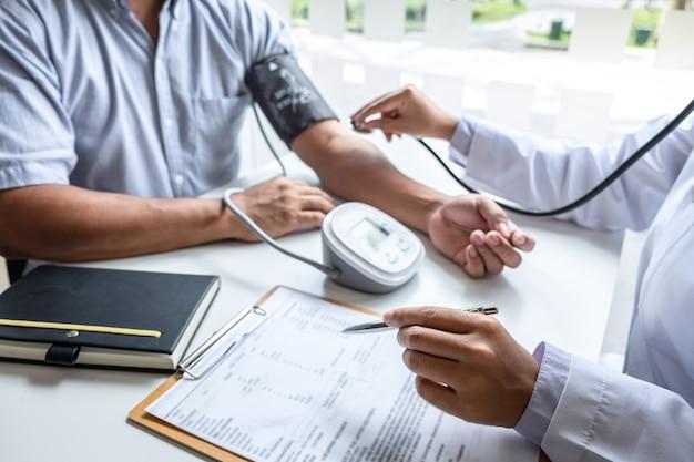 청진기를 사용하여 병원에 있는 환자에게 팔의 동맥혈압을 측정하는 의사.
