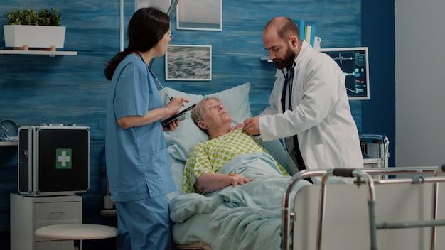 아픈 환자의 심장 박동 검사를 위해 청진기를 사용하는 의사