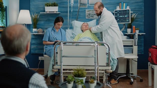 病院のベッドで病気の年配の女性に聴診器を使用して医師