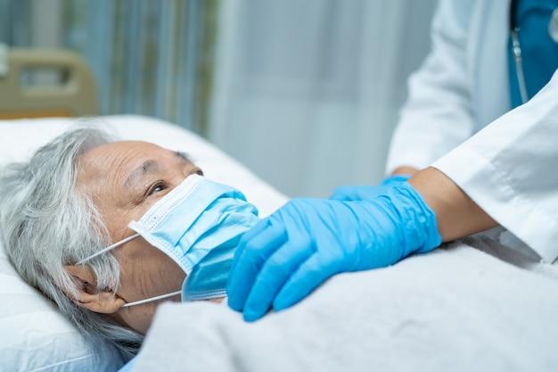 얼굴 마스크를 쓰고 아시아 고위 여자 환자를 확인하기 위해 청진기를 사용하는 의사