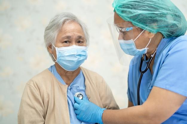 聴診器を使用して、感染を防ぐために病院でフェイスマスクを着用しているアジアの高齢者または高齢の老婦人女性患者をチェックする医師covid-19コロナウイルス。