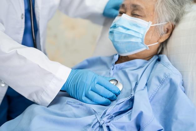 聴診器を使用して、感染を防ぐために病院でフェイスマスクを着用しているアジアの高齢者または高齢の老婦人女性患者をチェックする医師covid19コロナウイルス