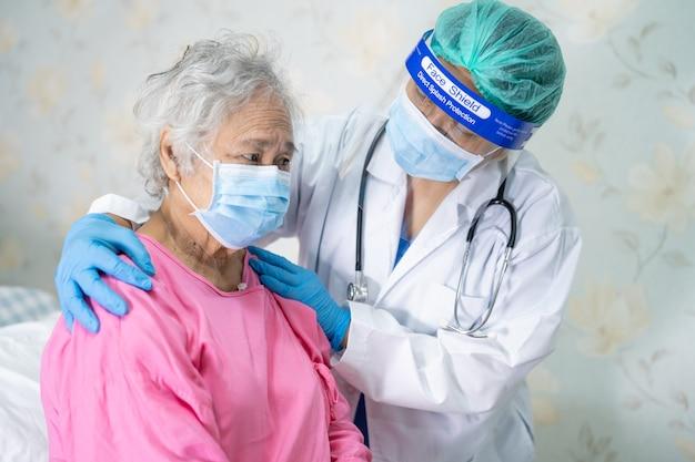 聴診器を使用して、covid-19コロナウイルスを保護するためにフェイスマスクを着用しているアジアの年配の女性患者をチェックする医師。