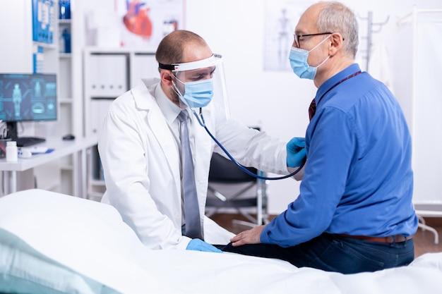 聴診器を使用して病室での検査中に高齢者の心臓を聞き、コロナウイルスに対する安全対策としてバイザーを着用している医師