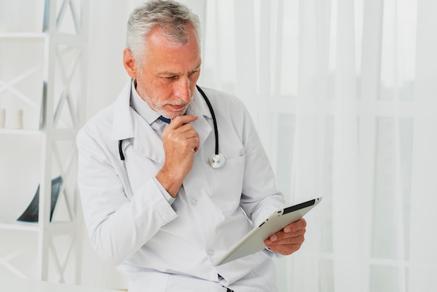 Doctor using tablet while hand is on chin