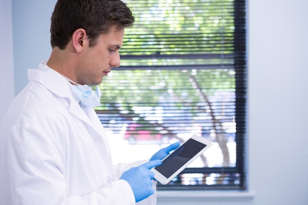 Doctor using tablet while standing against wall