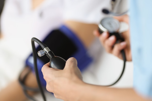 Doctor using tonometer checking blood pressure to patient in hospital medical assistance