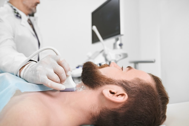 Doctor using ultrasound probe for lymph node diagnosis.