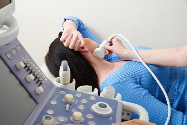 Doctor using ultrasound scanning machine examining female neck