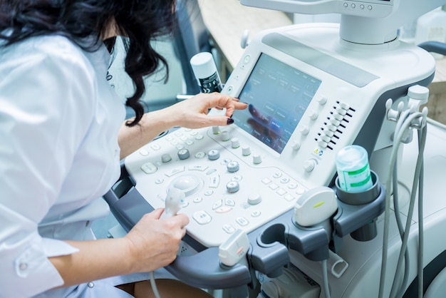 Doctor using ultrasound scanning machine for examining a thyroid of woman.