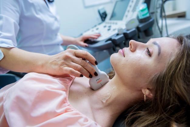 Врач с помощью аппарата ультразвукового сканирования для исследования щитовидной железы женщины