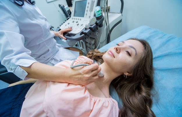 여성의 갑상선 검사를 위해 초음파 스캐닝 기계를 사용하는 의사