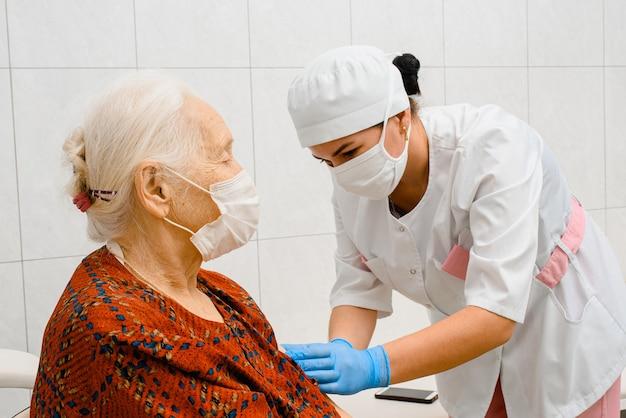 Врач вакцинирует пожилую женщину в хирургической маске
