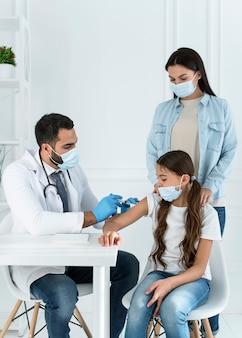 彼女の母親に支えられている少女に予防接種をする医者