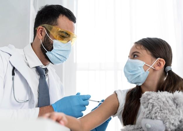 小さな女の子に予防接種をする医者