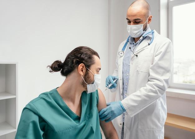 クリニックで患者に予防接種をする医師