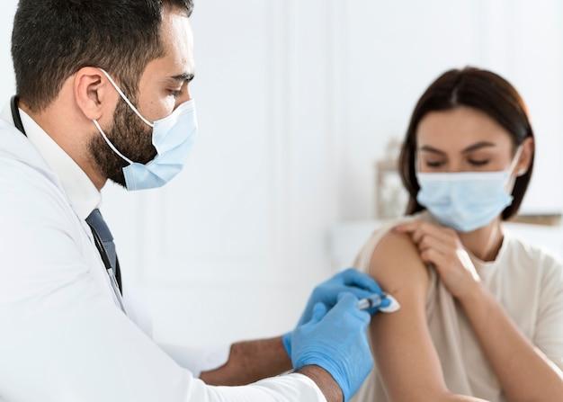젊은 여자를 예방 접종하는 의사