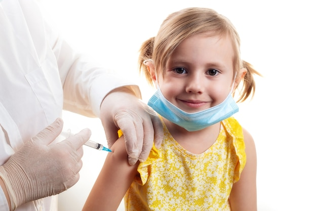 黄色のドレスと顔の保護マスクを身に着けているかわいい笑顔の少女にワクチンを接種する医師