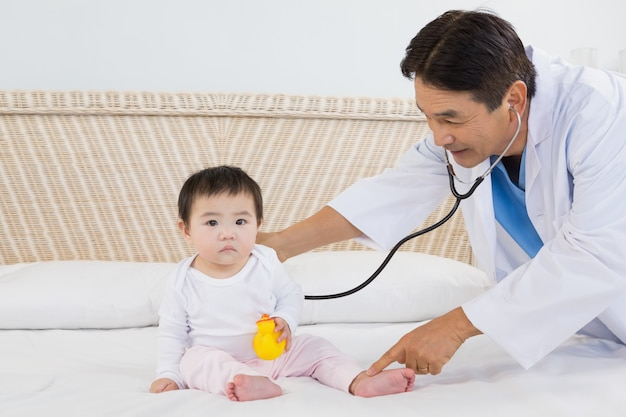 Doctor visiting cute baby on bed