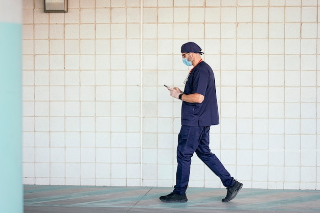 スマートフォンを使用して病院の外を歩く医師