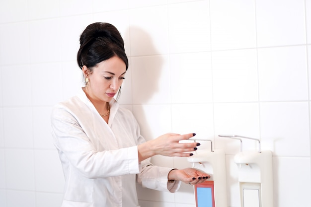 A doctor washing his hands using a disinfectant dispenser.
