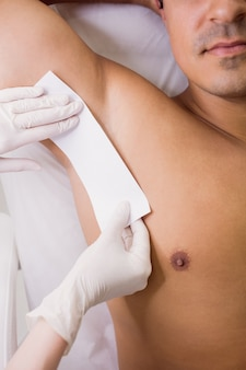 Doctor waxing male patient skin in clinic