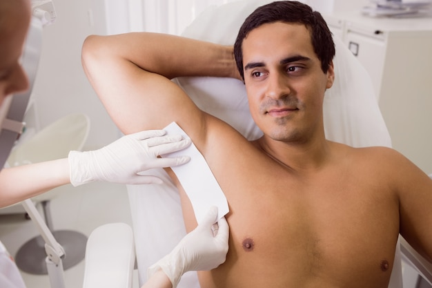 Doctor waxing male patient skin