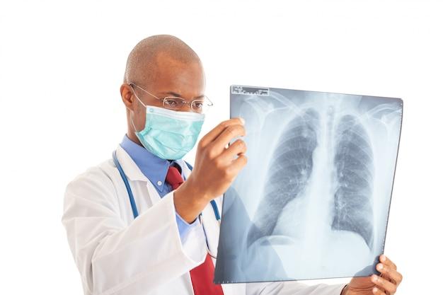 肺のレントゲン写真を保持しながらマスクを身に着けている医者